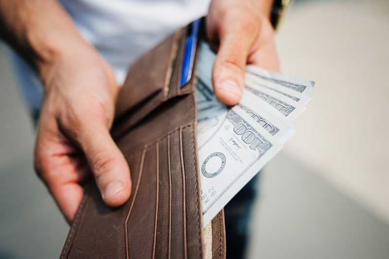man pulling out dollar bills from his wallet