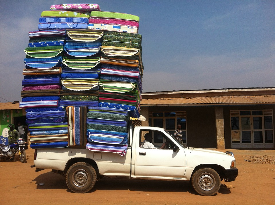 Bunch of mattresses stacked to eachother on top of a truck